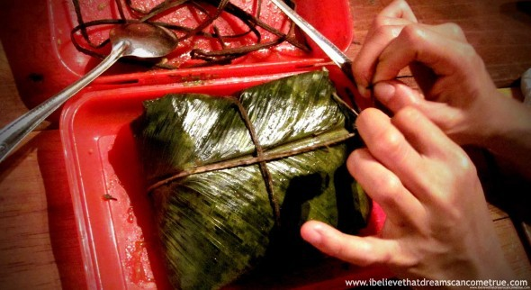 Tamale de arroz wrapped in banana leaves