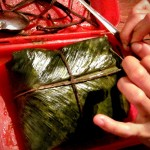 Tamale de arroz wrapped in banana leaves